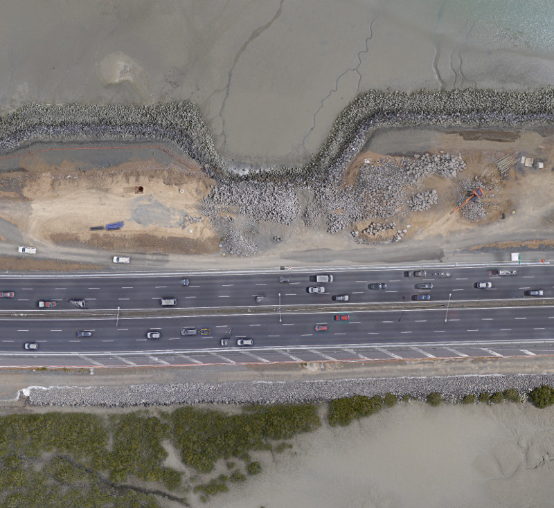Low tide exposes interface between road construction and seafloor
